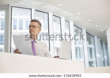 Thoughtful businessman with laptop and documents at railing - stock photo