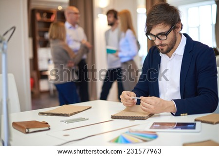 Thoughtful businessman with pen looking at empty notebook page at workplace - stock photo