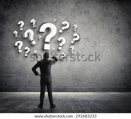 Thoughtful businessman with questions marks  - stock photo