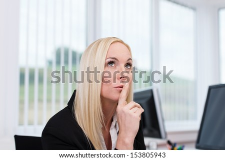 Thoughtful businesswoman making decisions sitting at her desk looking up into the air with her finger to her lips - stock photo