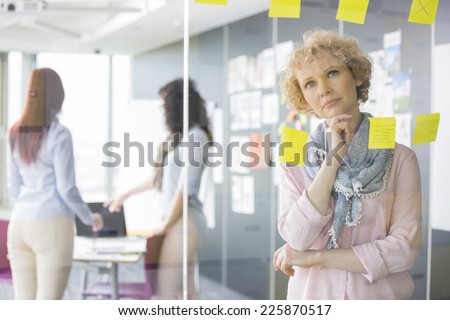 Thoughtful businesswoman reading sticky notes on glass with colleagues in background - stock photo