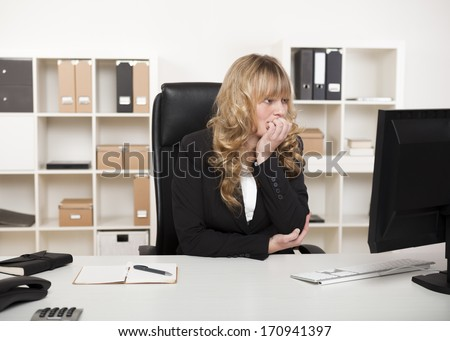 Thoughtful businesswoman sitting at her desk in the office reading her monitor on her desktop computer with her chin resting on her hand - stock photo