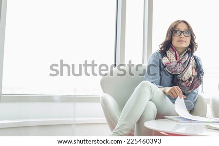 Thoughtful businesswoman sitting at table in creative office - stock photo