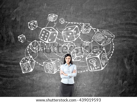 Thoughtful businesswoman standing against chalkboard with connected dice sketch. Game and probability theory - stock photo