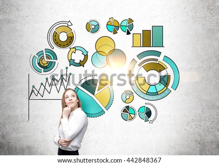 Thoughtful businesswoman standing against concrete wall with business pie charts - stock photo