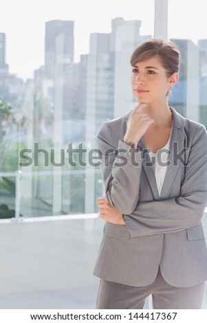 Thoughtful businesswoman standing in bright office - stock photo