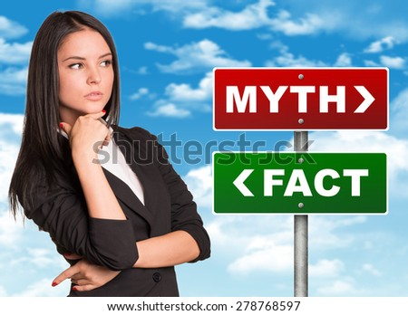 Thoughtful businesswoman standing near colorful myth and fact signboards and looking right side on blue sky background - stock photo