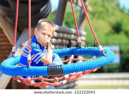 thoughtful child boy or kid in playground on leisure equipment - stock photo