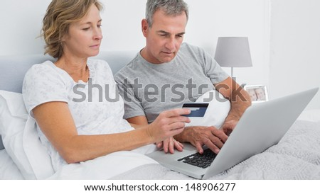 Thoughtful couple using their laptop to buy online at home in bedroom - stock photo