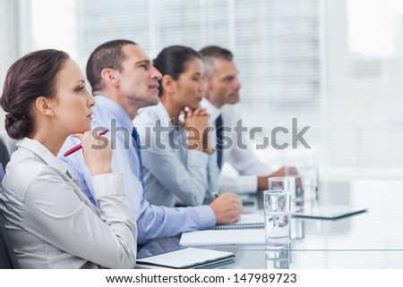 Thoughtful coworkers listening to presentation in bright office - stock photo