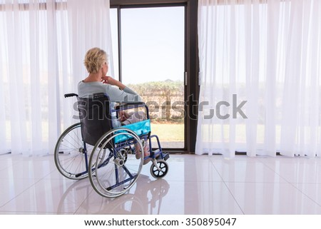 thoughtful disabled woman in wheelchair looking through door glass - stock photo