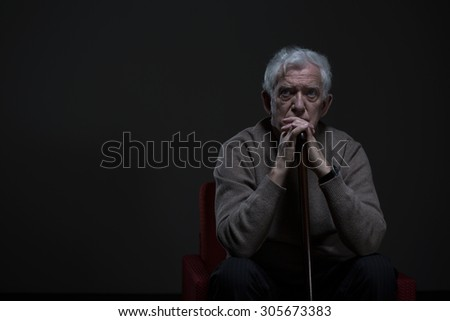 Thoughtful elder man sitting in a dark room - stock photo