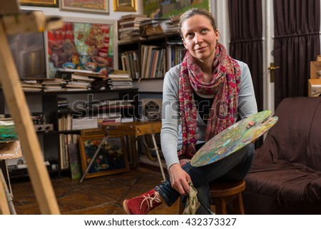 Thoughtful female artist sitting in a gallery holding a colorful artists palette and paintbrush in her hand and dreaming - stock photo