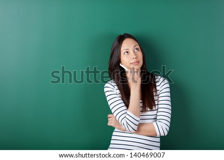 thoughtful female student leaning against blackboard in school - stock photo