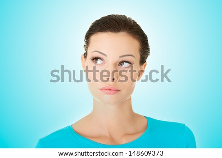 Thoughtful female student looking up - stock photo