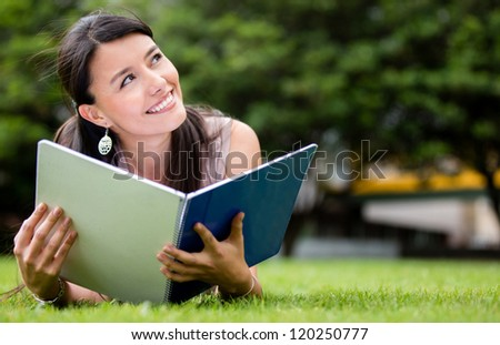 Thoughtful female student lying at the park - stock photo