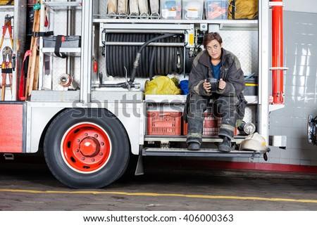 Thoughtful Firewoman Sitting In Truck - stock photo