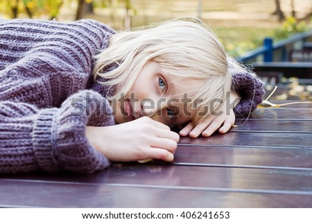 Thoughtful girl in a warm sweater, put her head on the table and resting - stock photo