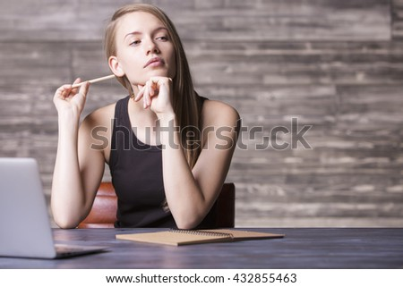 Thoughtful girl in tank top and pencil in hand sitting at wooden desk with laptop and notepad - stock photo