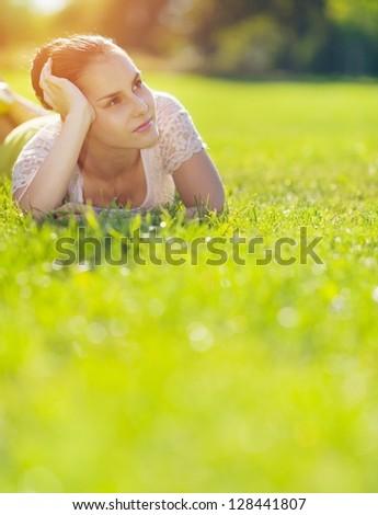 Thoughtful girl laying on meadow - stock photo