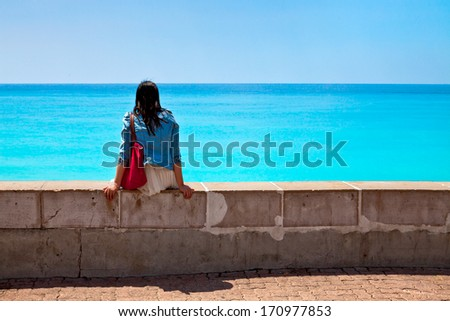 Thoughtful girl on the beach. Seascape. - stock photo