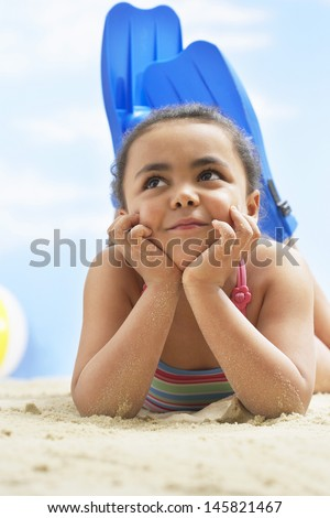 Thoughtful girl wearing flippers while lying on beach - stock photo