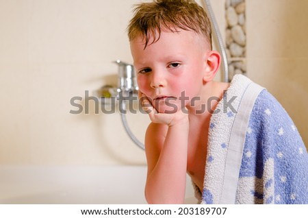Thoughtful glum little boy draped in a towel as he sits in the bathroom looking thoughtfully at the camera with his chin on his hand - stock photo