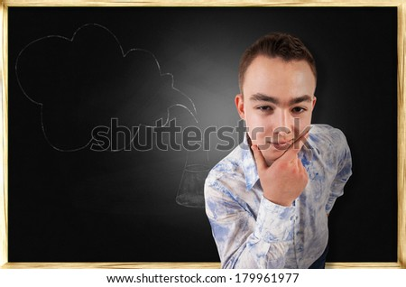 Thoughtful guy on black school board background - stock photo