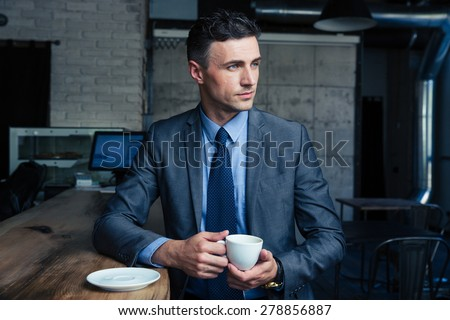 Thoughtful handsome businessman drinking coffee in cafe and looking away - stock photo