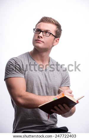 Thoughtful handsome. Concentrated young student with muscular body in eyeglasses reading book while sitting against white background - stock photo
