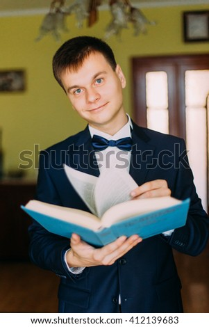 Thoughtful handsome man  in stylish blue suit and bow tie posing indoors with book standing by the window  - stock photo