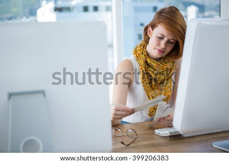 thoughtful hipster business woman sitting at her desk, browsing colour swatches - stock photo