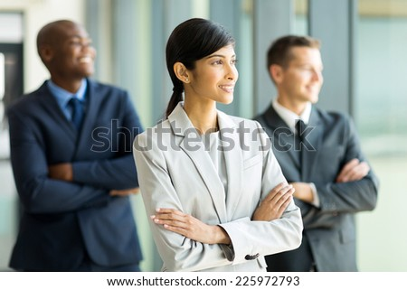 thoughtful indian businesswoman and colleagues looking outside window - stock photo