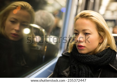 Thoughtful lady riding on a subway and looking out the window. Reflection of her face can be seen in the window. - stock photo
