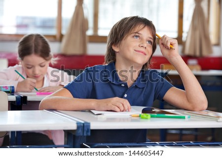 Thoughtful little boy smiling while looking up with classmate in background at classroom - stock photo