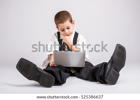 Thoughtful little business boy looking at his laptop - stock photo