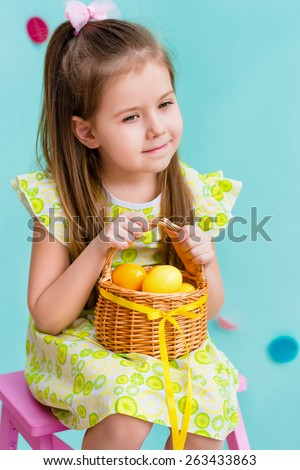 Thoughtful little girl with long blond hair wearing pink bow and holding wicker basket with yellow eggs and ribbon sitting on pink chair. Easter celebrations. Turquoise background. Studio portrait - stock photo