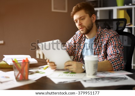 Thoughtful male person looking to the digital tablet screen while sitting in modern loft interior at the table, experienced entrepreneur reading some text or electronic book at the office - stock photo