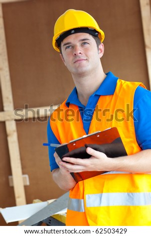 Thoughtful male worker holding a clipboard at work - stock photo
