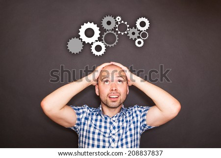 Thoughtful man and gear mechanizm against the black - stock photo