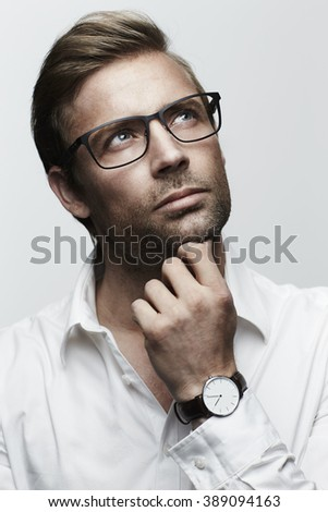 Thoughtful man in glasses, looking up - stock photo