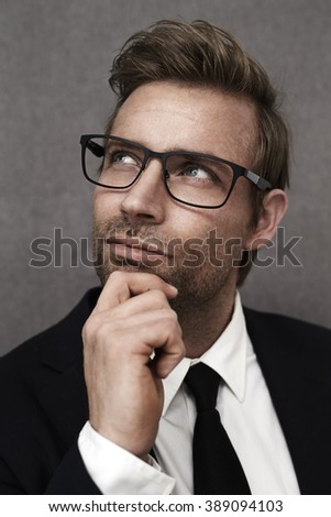 Thoughtful man in smart suit, looking up - stock photo