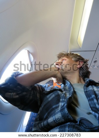 Thoughtful man on an airplane, Concept photo of air travel - stock photo