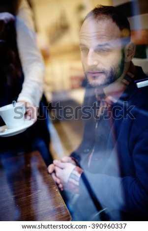 Thoughtful man sitting in cafeteria. Photographed through window. - stock photo