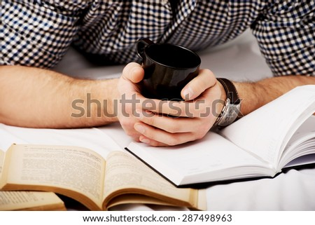 Thoughtful man with a book and coffee in his bed. - stock photo