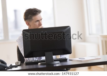 Thoughtful mature businessman looking away while sitting at computer desk in office - stock photo