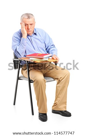 Thoughtful mature man sitting on a classroom chair isolated on white background - stock photo
