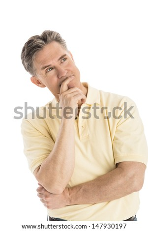 Thoughtful mature man with hand on chin looking away while standing over white background - stock photo