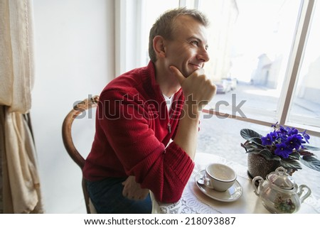 Thoughtful mid adult man sitting at table in cafe - stock photo