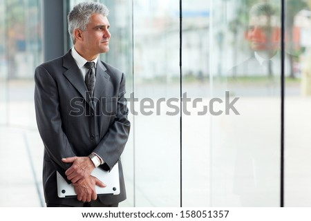 thoughtful mid age businessman looking through office window - stock photo